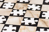 Blank puzzle pieces on chess board — Stock Photo