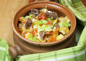 Meat and vegetables with sour cream and green celery in a pot — Stock Photo