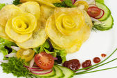 French fries in the form of a rose on a plate with a salad — Stock Photo