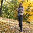 The young beautiful blond woman is walking in autumn park — Stock Photo