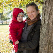 Young mother and her toddler son in autumn park — Stock Photo