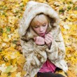 Stock Photo: Beautiful girl warms frozen hands in autumn park