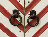 Forged ring at the gate in a red and white striped — Стоковое фото