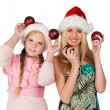Two girls in red christmas hats hold red fir-tree spheres in han — Stock Photo