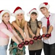 Four smiling teenagers in red christmas hats with fir-tree spher — Stock Photo