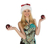 Girl in red christmas hat holds red fir-tree spheres in hand on — Stock Photo