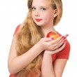 Attractive teen girl in the orange t-shirt holding an red apple — Stock Photo #46671999