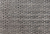 Wall from a dark brick with a pattern in a bright sunny day as a — Foto Stock