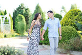 Young beautiful couple walking together in a park — Stock Photo