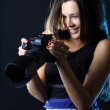 Woman with camera on a dark background looking at her great shot — Stock Photo