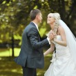Stock Photo: Happy young bride and groom dancing together outside on their we