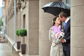 Bride and groom in a rainy day in an old town — Стоковое фото