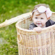 Cute little girl in a basket — Stock Photo