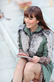 Beautiful woman using tablet in the park — Stock Photo