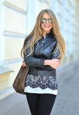 высокая мода модель носить солнцезащитные очки с мешок улыбаясь на открытом воздухе — Стоковое фото