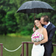 An excited wedding couple in a rainy day — Stock Photo