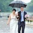 Young happy bride and groom walking by the rain — Stock Photo