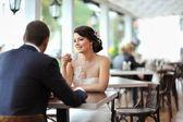 Junge glückliche braut und bräutigam sitzen in einem café im freien — Stockfoto