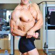 Male bodybuilder posing in gym — Stock Photo #14294231