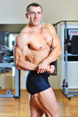 Male bodybuilder posing in gym — Stock Photo