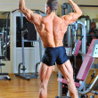 Bodybuilder posing at gym - back view full lenght portrait — Stock Photo #14322015