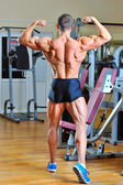 Bodybuilder posing at gym - back view full lenght portrait — Stock Photo