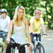 Portrait of pretty young woman with bicycle in a park and two me — Stock Photo