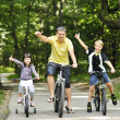 Family in the park on bicycles — Stock Photo