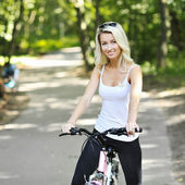Portrait of pretty young woman with bicycle in a park smiling - — Stock Photo