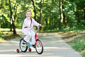 Portrait of cute boy on a bicycle smiling and resting his chin o — Stock Photo