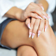 Stock Photo: Womnails with hands lying on her legs