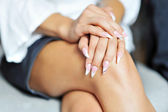 Woman nails with hands lying on her legs — Stock Photo