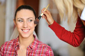 Make-up artist in action on beautiful face — Stock Photo