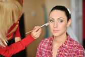 Make-up artist in action on beautiful woman face — Stock Photo
