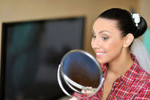 Beautiful woman looking in a mirror after applying makeup — Stock Photo