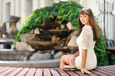 Young beautiful girl sitting on a bench near a copyspace — Stock Photo