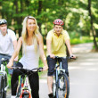 Stock Photo: Portrait of pretty young womwith bicycle in park with two m