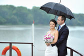 Bride and groom in a rainy weather on a boat — Stock Photo