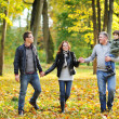 Happy family walking together in a park - Stock Photo