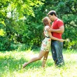 Happy young couple kissing outdoor in the park — Stockfoto