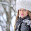 Young woman in a snowy furry hat — Stock Photo