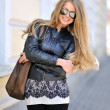 Beautiful woman in sunglasses with handbag  — Stock Photo