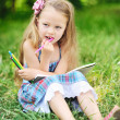 Little girl with color pencils in a park — Stock Photo