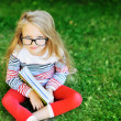 Little girl with a book in a park wearing glasses portrait — Stock Photo #19382765
