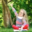 Little girl with a book in a park wearing glasses pointing at co — Stock Photo