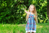 Little girl with soap bubbles in the park — Stock Photo