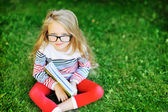 Little girl with a book in a park wearing glasses portrait — Stock Photo