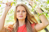 Portrait of beautiful woman in blooming tree in spring — Stock Photo