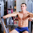 Stock Photo: Bodybuilder training chest on simulator