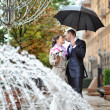 Kissing wedding couple in a rainy wedding day — Stock Photo
